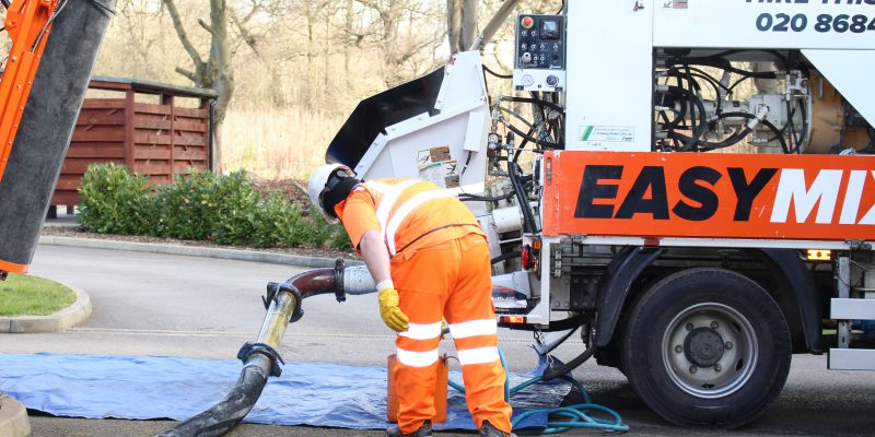 Easymix Concrete employee inspects ground pump on the lorry